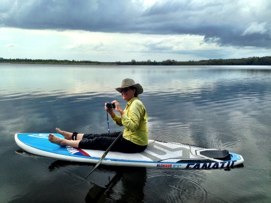 floating on a paddleboard under cloudy skies in DeLeon Springs State Park, Florida